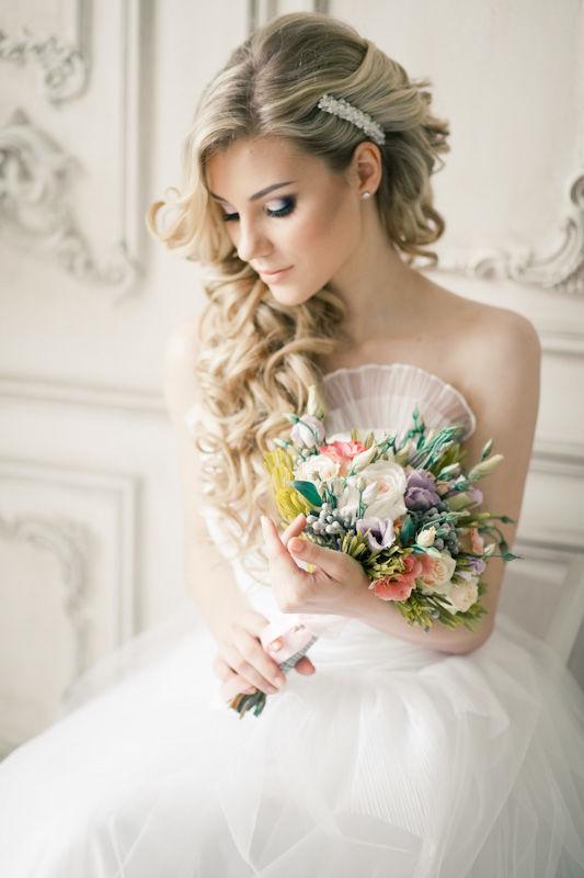 Свадебная прическа невесты заколотая на бок заколкой